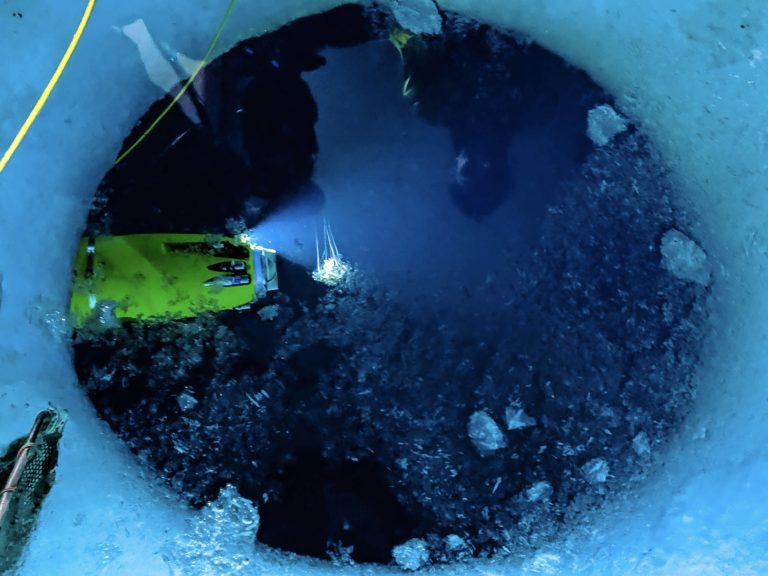 Picture of a hole in ice, with dark ocean beneath the ice. In the water, the yellow Icefin Robot shines light on a small jellyfish near the robot.
