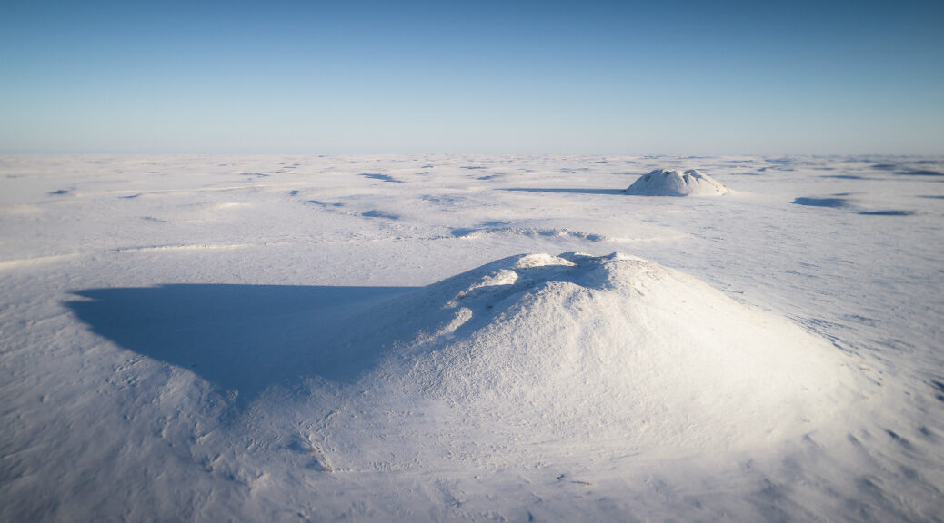 Ice-cored pingos emerge from permafrost and dot the arctic landscape near Tuktoyaktuk. Photo Credit: https://montecristomagazine.com/travel/northern-canada-ice-road