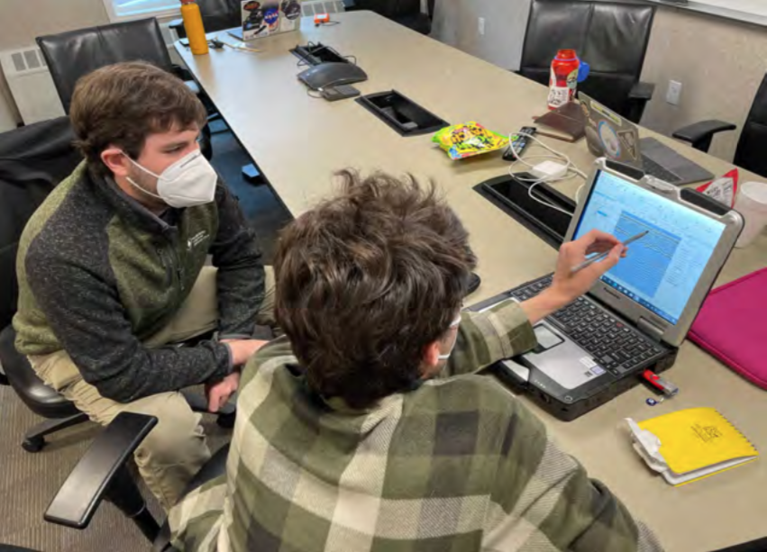 Photo of Team members discussing GPR data obtained over our first survey target affectionately referred to as Ringo (it presently does not have a recognized name).