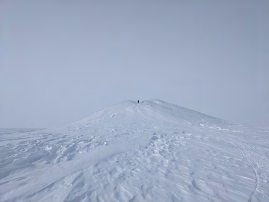 Photo showing Percy pingo, the tallest pingo that we will survey in the 2021 season, with a human at the summit for scale.