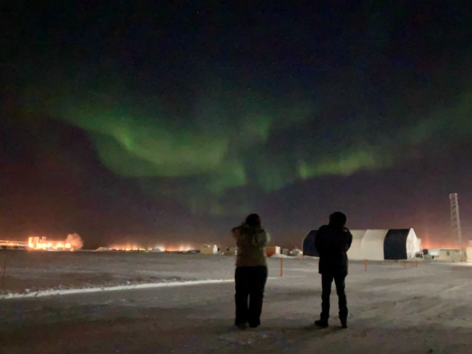 Photo of two people standing on snow covered ground, looking up at the green waves of the Northern Lights in the dark sky.